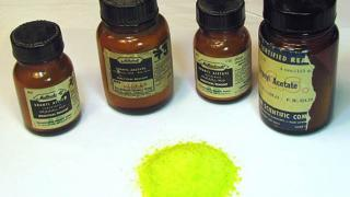 Bottles of uranium compounds with a small pile of yellow uranyl acetate powder